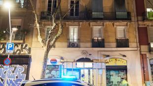 Un vehicle dels Mossos, davant l'edifici on s'ha produït el foc, al carrer Manso de Barcelona