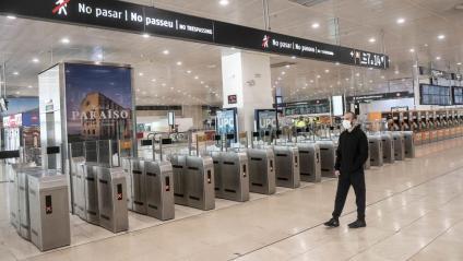 Un usuari del transport públic, ahir al matí, a l'estació de Sants, amb una afluència mínima