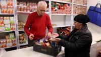 Una dona rep un lot de productes del Banc dels Aliments