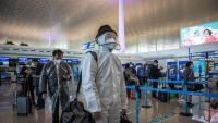 Passatgers protegits fan cua a l'aeroport per sortir de Wuhan cap a altres ciutat xineses