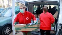 Una voluntària de la Creu Roja porta aliments a una persona gran