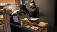 Una de les treballadores de la Fundació Drissa que fa de dependenta en una botiga de menjar cobrant la comanda d'un client