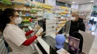 Una farmacèutica dispensa una mascareta a un client