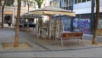 Un bar tancat amb tot el material de la terrassa apilat a la plaça del Pes de la Palla de Barcelona avui dilluns, primer dia que aquests negocis podien obrir amb restriccions