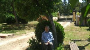 Francesc Casas a sota d'un arboç, al jardí de casa seva