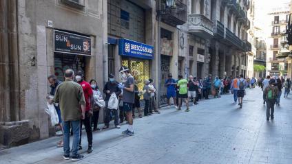 Llargues cues de gent esperant torn per a una bossa de menjar a les portes de la parròquia de Santa Anna