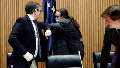 El vicepresident Iglesias saluda Patxi López amb l'encaixada de colzes típica del distanciament social, ahir al Congrés
