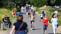 Ciutadans passegen, ahir, per un parc de Londres aprofitant el bon temps