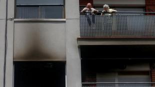 Uns veïns miren el pis cremat des del seu balcó