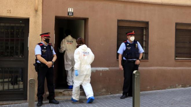 Agents de la Policia Científica dels Mossos d'Esquadra entren a l'edifici del domicili d'Esplugues de Llobregat on han assassinat una dona