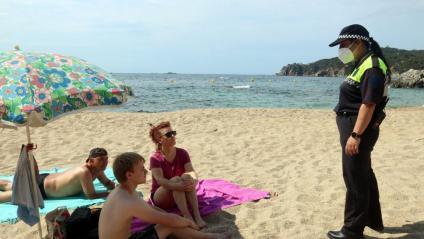 Una agent cívica informa sobre les normes que regeixen a les platges de Calella, al Maresme