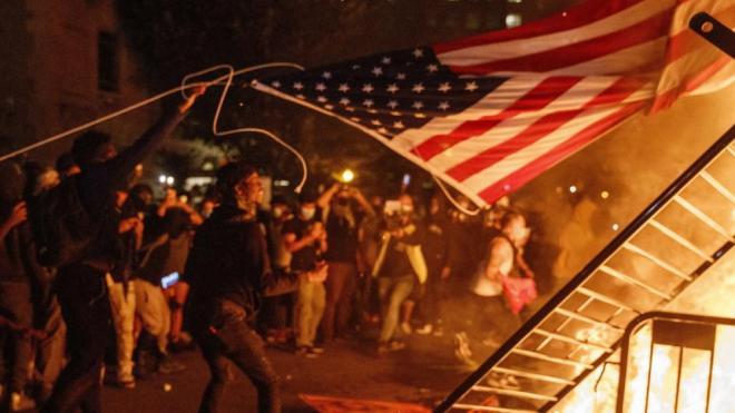 Manifestants llancen una bandera nord-americana al foc a la ciutat de Washington en la setena nit de protestes contra el racisme