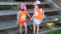 Dues nenes de la mà, amb mascareta, en el primer dia de casal d'estiu