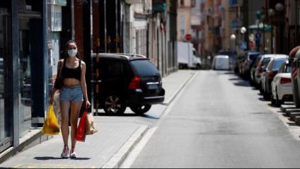 Una veïna del barri de la Torrassa, a l'Hospitalet de Llobregat, caminant ahir amb mascareta i unes quantes bosses de la compra