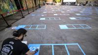 Un treballador marca al terra la distància social