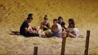 Un grup de persones fan el 'botellón' a la platja de la Barceloneta de Barcelona