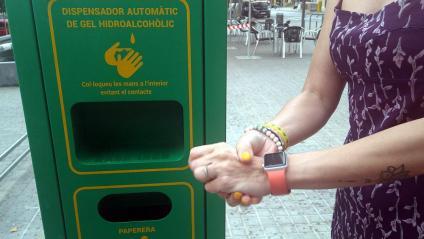 Una dona es renta les mans en un dels dispensadors que ha instal·lat l'Ajuntament de Sabadell a la ciutat