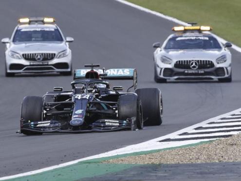 El Mercedes de Hamilton, escortat pel cotxe de seguretat i el vehicle mèdic, en la volta de descerelació, amb el pneumàtic destrossat
