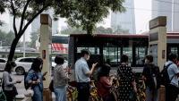 Xinesos amb mascareta fan cua per agafar l'autobús a Pequín