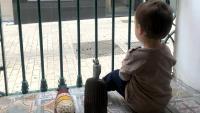 Un nen mira per la finestra de casa, durant el confinament