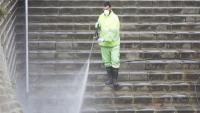 Un treballador municipal desinfecta unes escales a Nou Barris