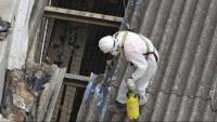 Un operari retira una teulada d'amiant