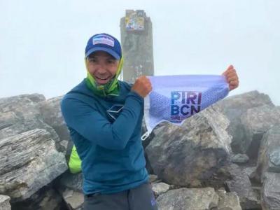 Mingote al cim del Mont Olimp mostrant el banderí de la candidatura dels Jocs Olímpics d'hivern Pirineus-Barcelona 2030