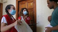 Dues voluntàries de la Creu Roja entregant material escolar a una família