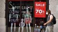 Un home passa per davant d'una botiga amb descomptes de fins al 70%, ahir, a Londres