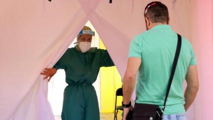 Una sanitària atén un noi que es vol fer una prova PCR a Terrassa dins de la campanya de cribratge massiva a la ciutat vallenca organitzada per la conselleria de Salut