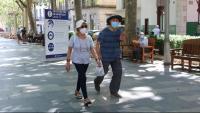 Una parella passeja davant un cartell amb recomanacions contra la Covid-19 a Figueres