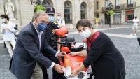 El president del RACC , Josep Mateu i la regidora de Mobilitat de l'Ajuntament de Barcelona, Rosa Alarcón, col·loquen un adhesiu de la campanya a una moto compartida