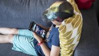 Un nen jugant amb un dispositiu digital a casa seva