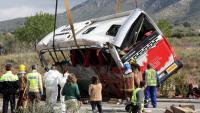 Efectius mirant com la grua està aixecant l'autobús accidentat a l'AP-7 a Freginals