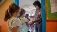 Una mestra dispensa gel hidroalcohòlic a l'escola de Taialà