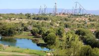 Terrenys del Centre Recreatiu i Turístic (CRT) de Vila-seca i Salou, amb un llac i camp de golf de PortAventura en primer terme, i les atraccions al fons