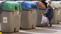 Una persona llença una bossa d'escombraries en un contenidor