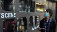 Un jove mira un aparador en un centre comercial de Pequín. L'economia xinesa tancarà l'any amb un 5,4% d'atur, mentre el país reprèn l'activitat