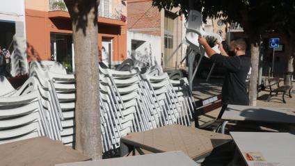 El propietari del bar El Caixer de Vilobí, Jordi López, recollint cadires