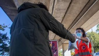 Una voluntària entrega una bossa amb menjar a una persona que viu al carrer a Girona en una sortida de la Creu Roja divendres passat