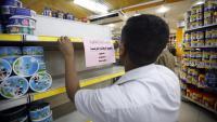 Un treballador enganxa un cartell que anima a boicotejar productes francesos en un supermercat de Sanà (Iemen)