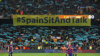 Cartell de Tsunami Democràtic amb el lema 'Spain, sit and talk!' a l'inici del clàssic al Camp Nou darrere dels jugadors, el 18 de desembre del 2019