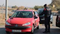 Control policial ahir a Alcarràs, on un agent revisa un certificat d'autoresponsabilitat
