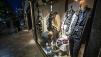 Un comerciant muntant l'aparador de la seva botiga del carrer Santa Clara de Girona