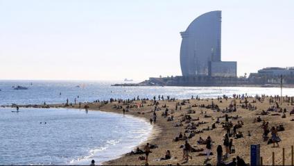 Grups de persones a la platja de la Barceloneta, amb la silueta de l'Hotel Vela al fons, el primer cap de setmana amb el confinament perimetral dels municipis