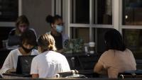 Clientes d'un bar treballant amb ordinadors i amb la màscara posada a Los Angeles (Califòrnia)