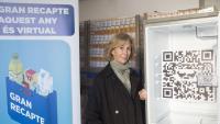 Roser Brutau,  al Banc dels Aliments, entre un cartell del Gran Recapte  i una nevera buida, metàfora de la necessitat, amb el codi QR per participar-hi