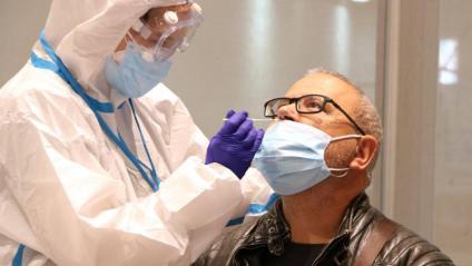 Un sanitari pren una mostra per fer una prova PCR a un pacient al Centre Cívic Cal Balsach de Sabadell