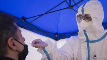 Una professional sanitària agafa una mostra per fer un test ràpid de Covid-19