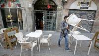 Un petit empresari obre el seu establiment, a Barcelona, aquest dilluns